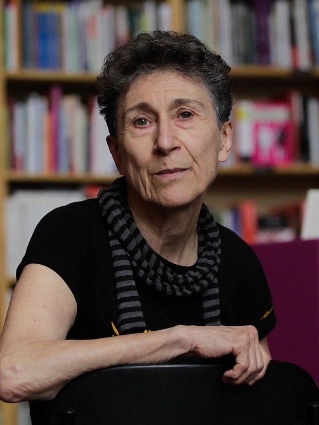 Image of Silvia Federici, sitting on a chair while turned to the camera.