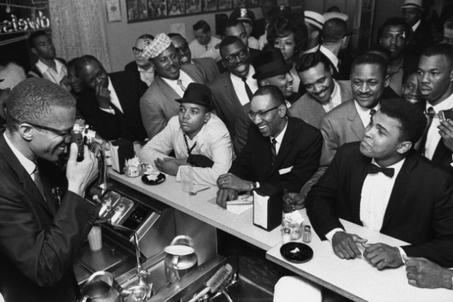 Malcolm X behind the counter at a restaurant, photographing Cassius Clay.